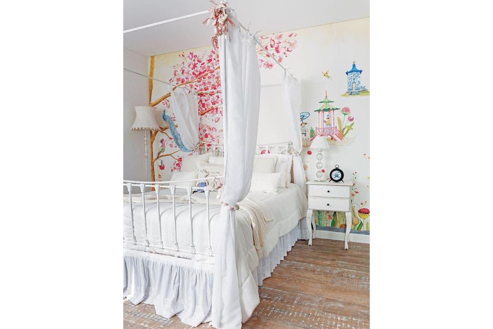 La cama de hierro con baldaquino, cortinas de gasa y un sillón rosado capitoné ($9.040, todo de Agustina Cerato).  Foto:Living /Javier Csecs