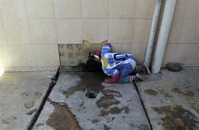 Un chico de la villa 20 toma agua de una canilla sobre las cloacas del barrio