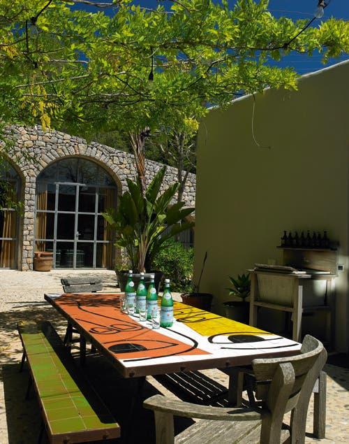Afuera, una mesa de estilo rústico lista para el encuentro y para deleitarse con un maravilloso paisaje.