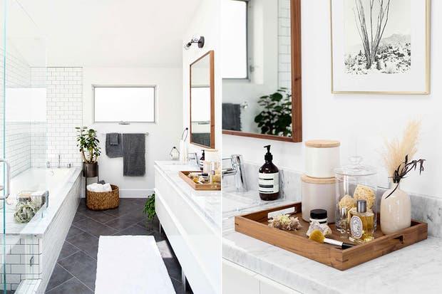 Los detalles son fundamentales y este baño es una gran muestra de ello: el canasto de ratán, la bandeja con contenedores y perfumes, y el cuadro a un lado del espejo son algunos de los recursos que le dan estilo a este espacio de base neutra.  /100layercake.com