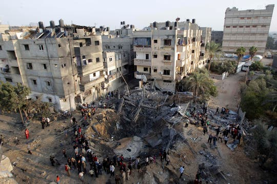 Los palestinos se reúnen alrededor de una casa destruida tras un ataque aéreo israelí en Khan Younis, en el sur de la Franja de Gaza. Foto: Reuters