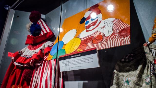 Uno de los dibujos de Gacy y alguna de su vestimenta en el Museo Nacional del Crimen, Estados Unidos.