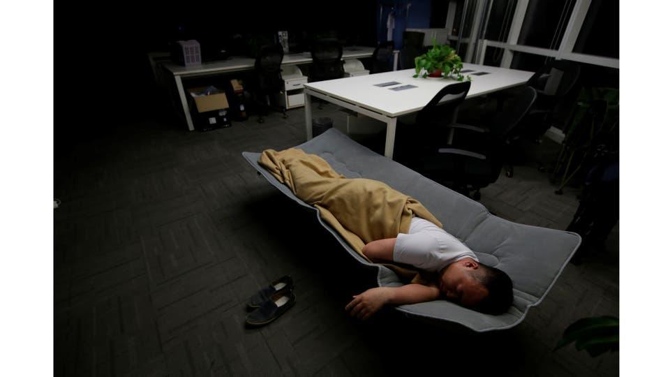 Ma Zhen Guo, un ingeniero de sistemas en Renren crédito Management Co., duerme en una cama plegable en la oficina después de terminar el trabajo temprano en la mañana