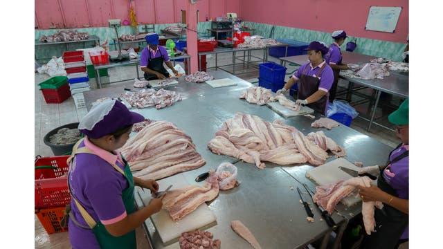 Trabajadores procesan carne de cocodrilo en un matadero en las afueras de Bangkok