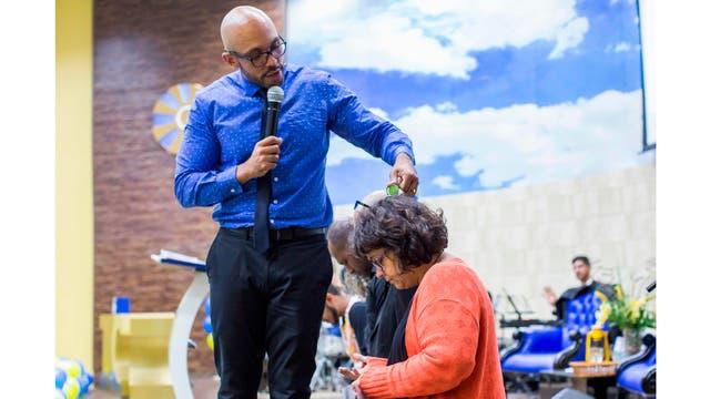 El pastor Fabio de Souza, vierte agua sobre los fieles durante el servicio dominical