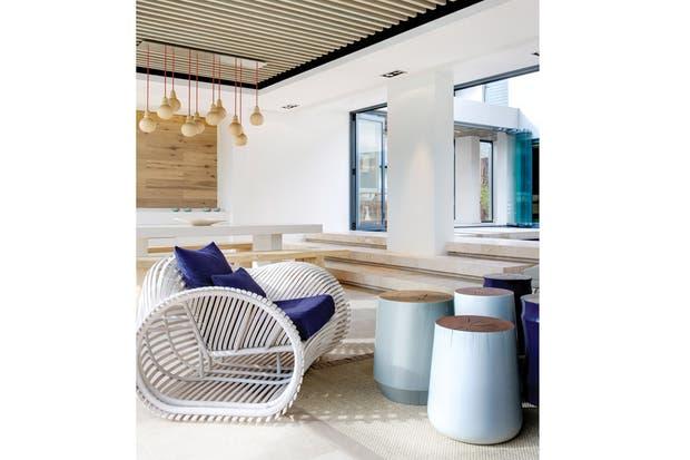 La galería conectada con el patio interior. Allí, mesas de arrime hechas a partir de grandes troncos, a tono con el almohadón del sillón Lolah diseñada por Kenneth Cobonpue..