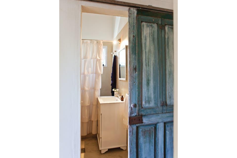 Además de revestir todas las superficies en microcemento, en el baño se cambiaron todos los artefactos sanitarios y de iluminación. Como es bastante pequeño, el ingenio de Gabi decantó por una puerta corrediza antigua que facilitara el acto mecánico de abrir y cerrar.  /Javier Picerno