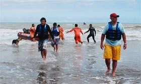 Los tres pescadores, en el momento de llegar a tierra, tras ser rescatados por hombres de la Prefectura