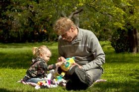 Gerardo Freideles, de 53 años, y su hija Juana, de 1 año y medio, juegan en el parque de su casa en Núñez