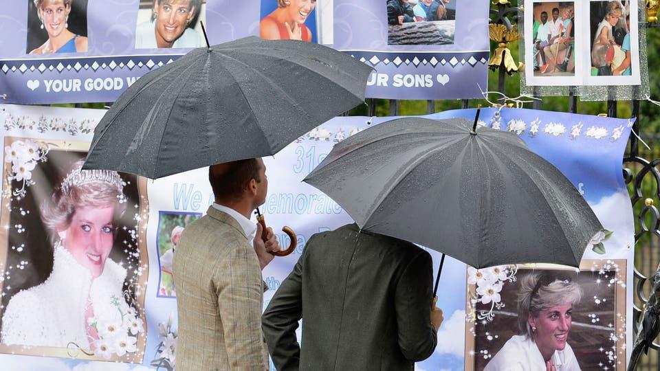 El Príncipe William de Gran Bretaña, a la izquierda, y el Príncipe Harry miran algunas fotos en las Puertas Doradas del Palacio de Kensington. Foto: AP / John Stillwell