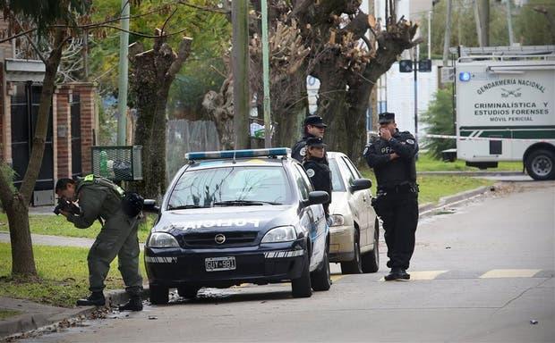 Un perito de la Gendarmería fotografía evidencias mientras policías de la Federal custodian la escena del hecho