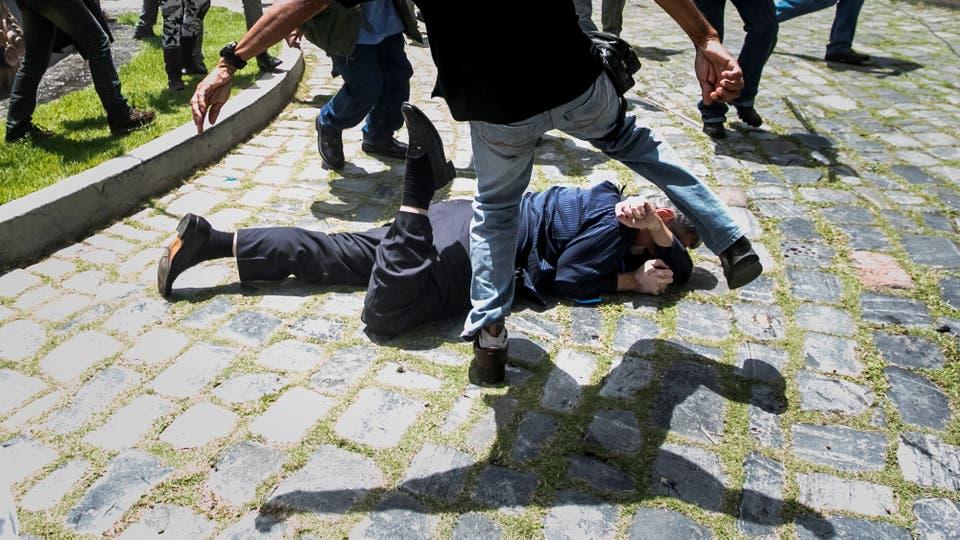 El diputado Américo De Grazia (c) es golpeado por manifestantes en la Asamblea Nacional. Foto: EFE / Miguel Gutierrez