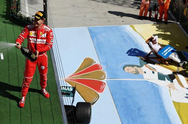 Vettel festeja su triunfo y abajo, Fernando Alonso recrea la imagen de un momento icónico de la Fórmula 1