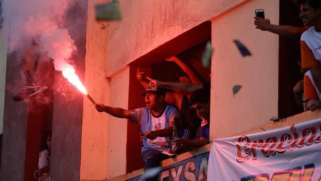 Un hincha enciende una bengala desde un balcon de un edificio para ver a los equipos de fútbol