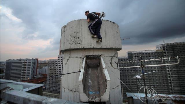 Vad Him del equipo Rudex sube a una estructura en un techo en Moscú