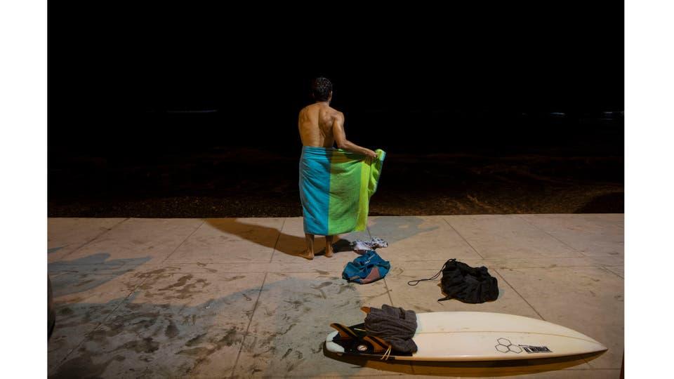 Un hombre se envuelve en una toalla luego de surfear por varias horas. Foto: AP / Rodrigo Abd