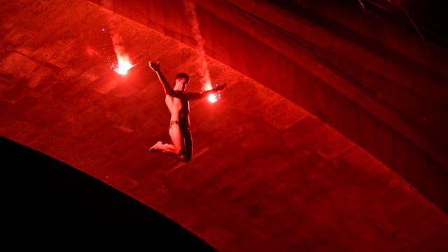 Un hombre salta con bengalas durante un show nocturno