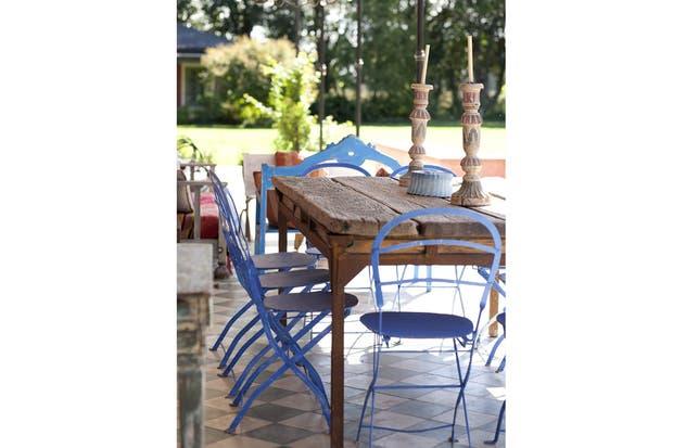 Sillas compradas en un remate se destacan con su azul marroquí, que realza su contraste con la pared roja.