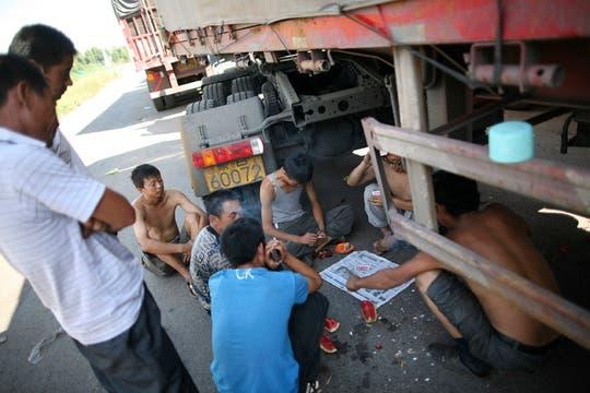 Un grupo de camioneros juega a las cartas mientras espera que el tráfico avance un poco, hace 10 días que este embotellamiento afecta a la autopista que conduce a Beijing. Foto: AP
