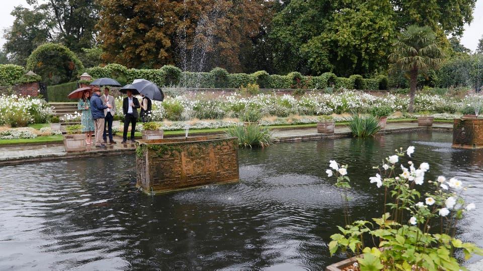 El Príncipe William de Gran Bretaña, su esposa Kate y el Príncipe Harry hacen un recorrido por el jardín conmemorativo en el Palacio de Kensington. Foto: AP / Kirsty Wigglesworth
