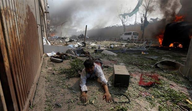 Un hombre gravemente herido se arrastra cerca de la escena del atentado en el centro de Kabul, tras el estallido del camión cisterna