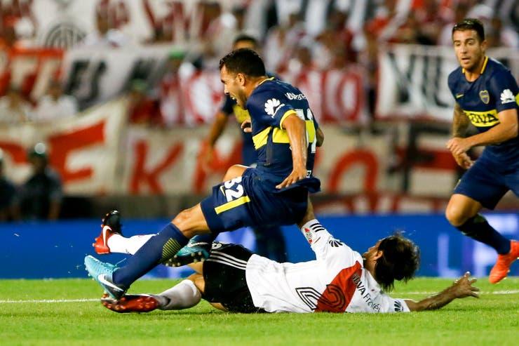 Carlos Tévez y Leo Ponzio luchan en el superclásico