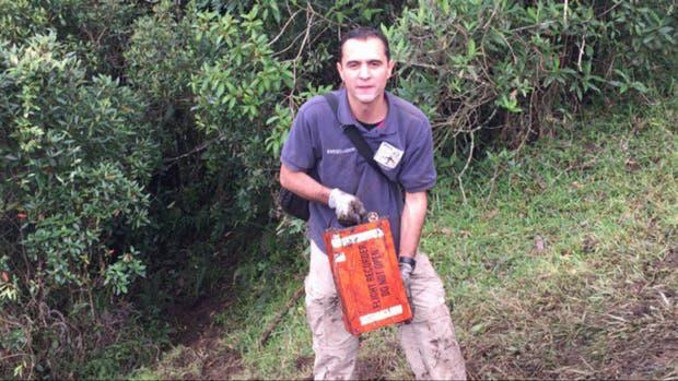 Personal de bomberos rescata una de las cajas negras del avión, que en realidad son color naranja