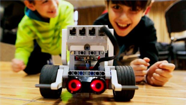 En primer plano, el robotito terminado; atrás, orgullosos, dos de sus creadores