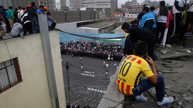 Los hincas pagan alrededor de $ 2 dólares para observan el partido desde la terraza de un edificio, durante el campeonato de fútbol callejero el Porvenir en Lima, Perú
