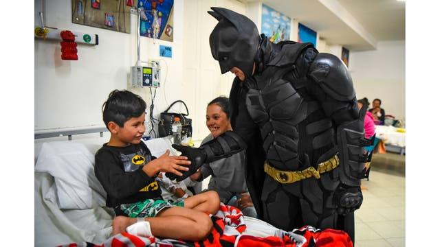 Pablo Valdez, de 7 años, internado por una infección que le impide caminar, mientras juega con Batman