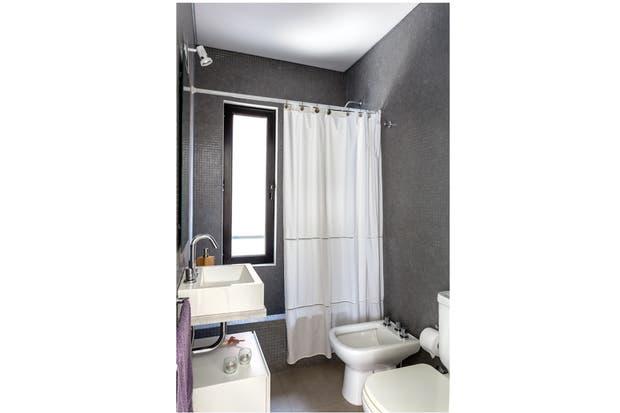 Sin cambios respecto de la propuesta original, se optó por mantener el estilo sobrio con una cortina blanca y un mueble laqueado a tono bajo la bacha.  /Daniel Karp
