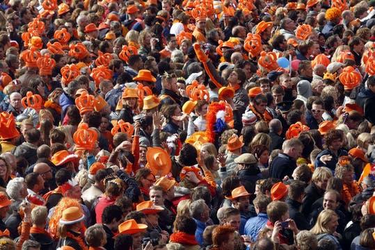 Con carteles y disfraces alusivos a la dinastía Orange, una multitud se congregó en la céntrica plaza Dam para darle la bienvenida a los nuevos reyes. Foto: AFP