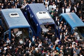 Los cuerpos de tres de las víctimas, subidos a camionetas durante su funeral