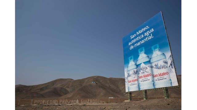 Cartel que anuncia agua de manantial se encuentra a lo largo de la Carretera Panamericana en un área donde la gente vive en hogares sin agua potable