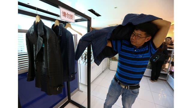 Un turista chino se prueba una chaqueta hecha de piel de cocodrilo en la granja de Sriracha