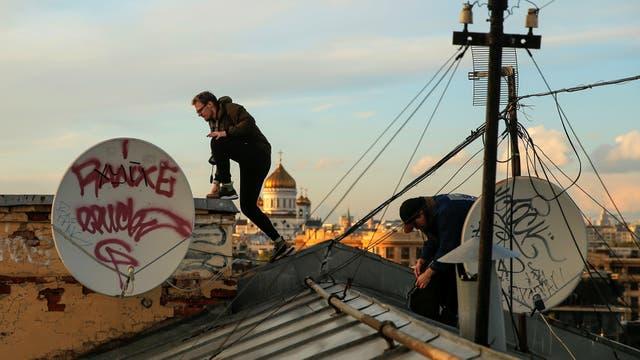Georgy Lanchevskiy y Konstantin Drykin mientras caminan por una cornisa de una terraza en Moscú, Rusia,