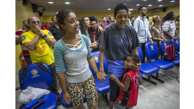 Katia Maria Soares, su compañera Carolina y su hijo participan en el servicio dominical