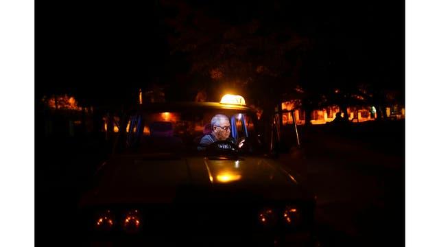 René Almeida habla con familiares que viven en los Estados Unidos en una llamada de video dentro de su taxi en un punto de acceso a Internet en La Habana