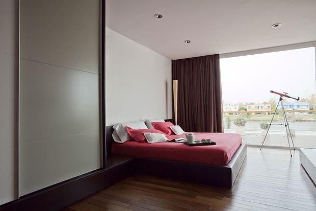 El cuarto principal juega con los marrones y los rojos, combinándolos en la cama y en las cortinas.
