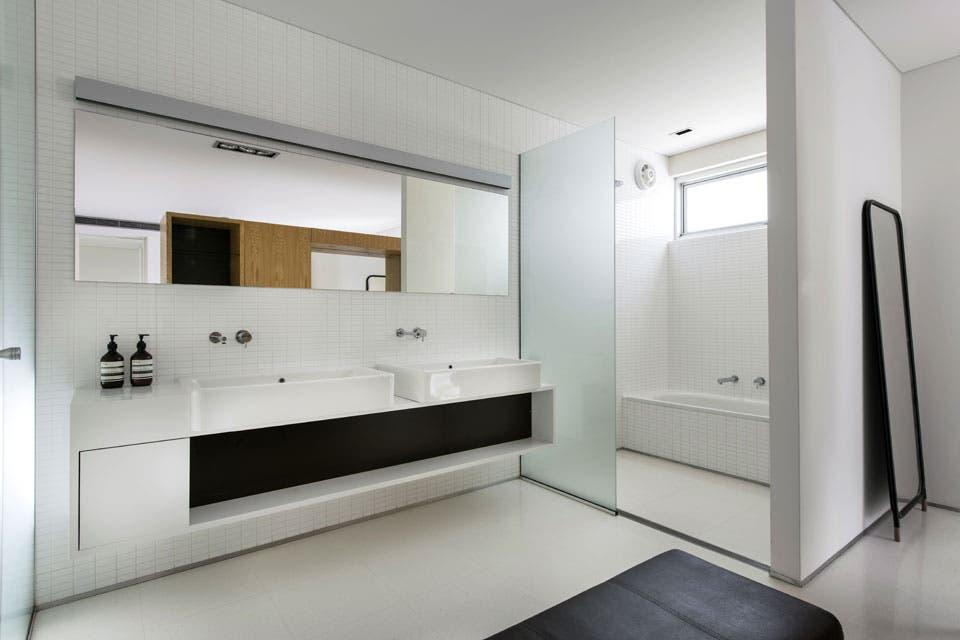 Bachas Para Baño Cuadradas:En paralelo al espejo, una mesada blanca con bachas cuadradas y mueble