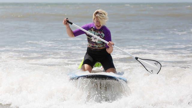 Patricia Casey toma clases de stand up paddle en Playa Grande, Mar del Plata, mientras su marido cuida a su hijo