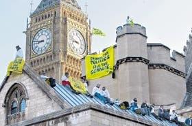 Con llamativos carteles, desde el techo del Parlamento, en Londres, los ambientalistas instaron a detener el avance del cambio climático