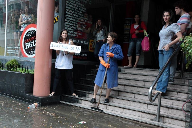 Una jóven muestra un cartel durante una inundación en Belgrano luego de un diluvio, 9 de noviembre. Foto: LA NACION / Ricardo Pristupluk
