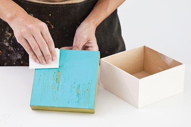 2. Pintar la tapa con acrílico color aguamarina y dejar secar bien antes de seguir. Decapar el acrílico con la ayuda de una lija, realizando mayor presión donde se desee levantar más pintura..