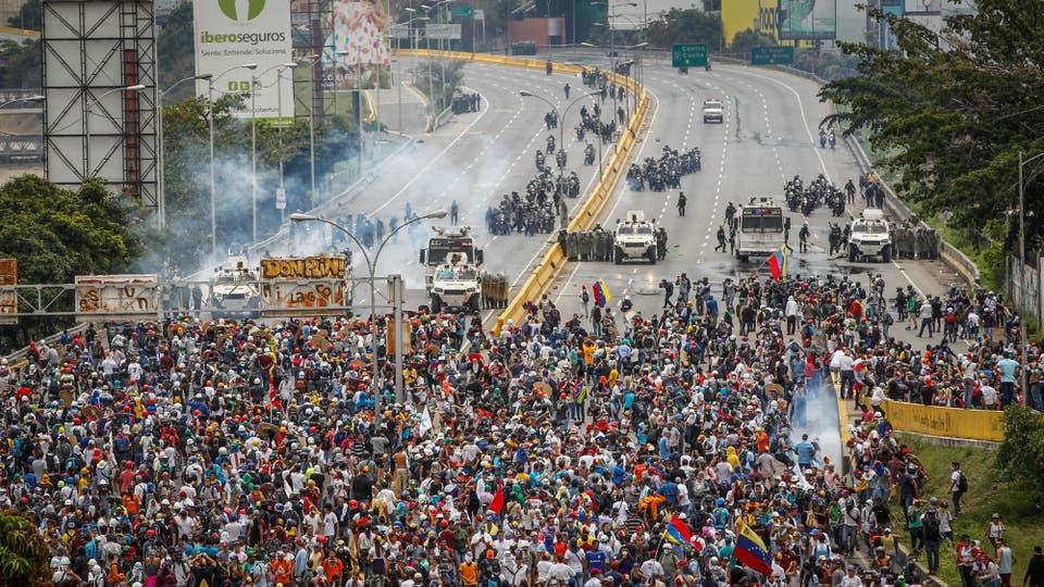 Manifestantes chocan contra la policía antidisturbios en Caracas. Foto: Reuters / Christian Veron