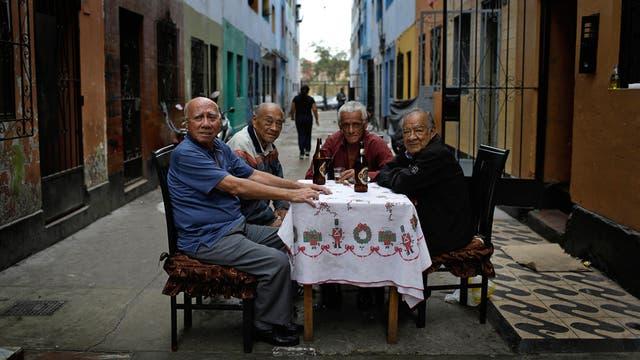 Teodoro Aquino, izquierda, bebe cerveza con sus amigos antes del inicio del campeonato de fútbol callejero el Porvenir en Lima, Perú