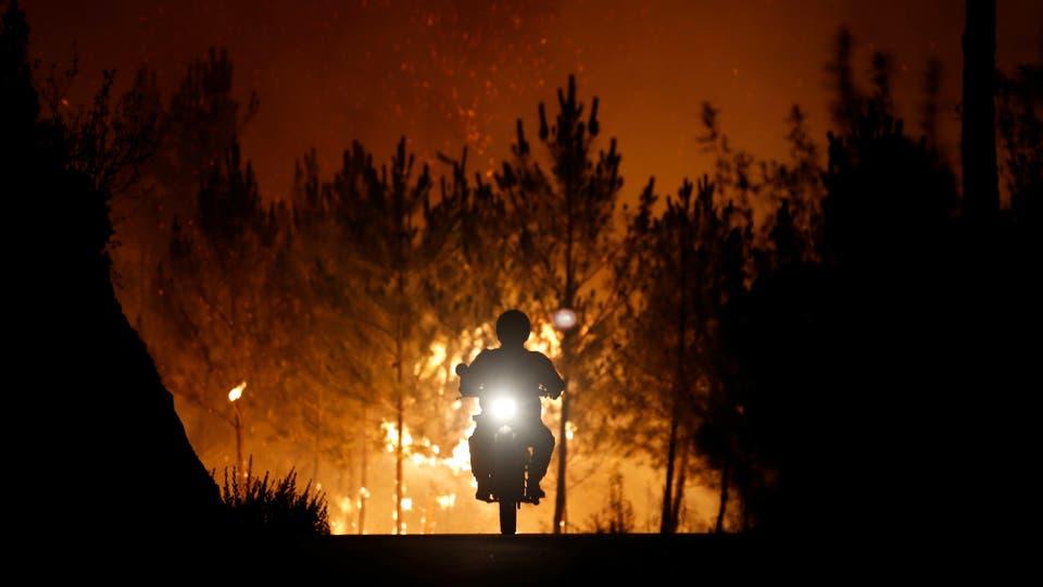 Un bombero montando una motocicleta, se aleja del fuego en la aldea de Macao, cerca de Castelo Branco, Portugal.