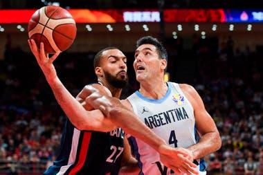 Luis Scola aguanta la grosera infracción del francés Rudy Gobert, de Utah Jazz, el mejor defensor de la NBA, que tampoco pudo detenerlo