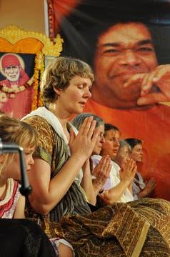 Creyentes de varias nacionalidades rezan por el alma del gurú. Foto: AFP