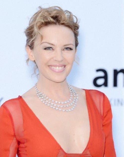 Kylie Minogue bellísima sobre la alfombra roja con un recogido con ondas bien marcadas.